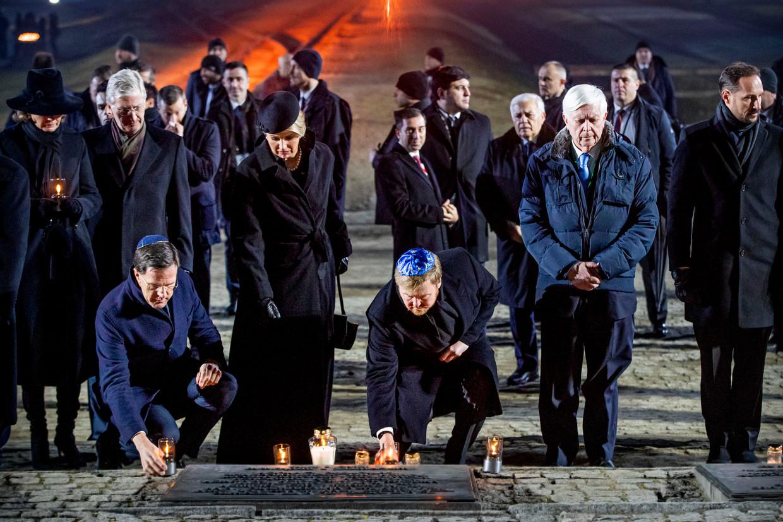 Mark Rutte, koningin Máxima en koning Willem-Alexander tijdens de herdenking van de bevrijding van Auschwitz in Polen. Beeld BSR Agency