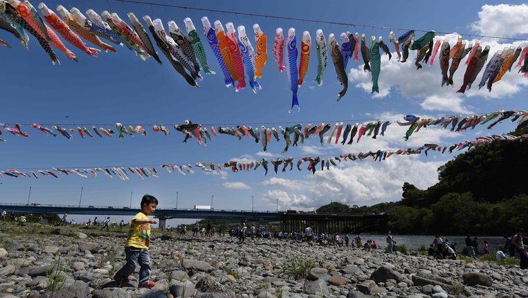 Een jongetje loopt onder wimpels met vlaggen van karpers door in een park in Sagamihara, in Tokio. De slingers worden ter ere van 'Kinderdag', dat jaarlijks op 5 mei valt, opgehangen.
