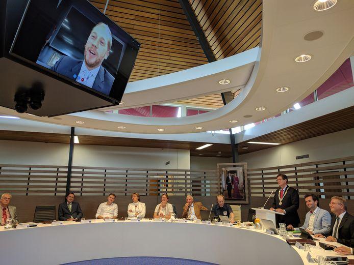 De bekendmaking van de naam van de nieuwe burgemeester, die zelf de vergadering via Skype bijwoont.