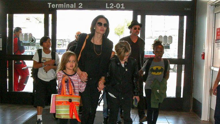 Actrice Angelina Jolie en acteur Brad Pitt vliegen met hun kinderen vanaf de luchthaven van Los Angeles. Beeld Photo News