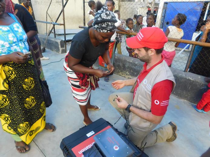 Jeroen Aanraad (met de rode pet) helpt in Mozambique namens Vodafone om de communicatiemiddelen te herstellen
