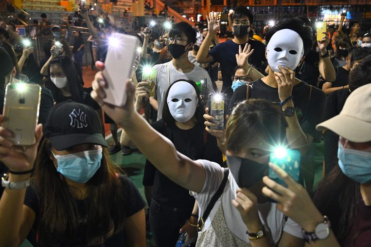 Demonstranten dragen maskers en gebruiken hun telefoon als zaklamp tijdens een flash mob in het district Sham Shui Po, een dag nadat gisteren in Hongkong een verbod op gezichtsbedekking is ingesteld.