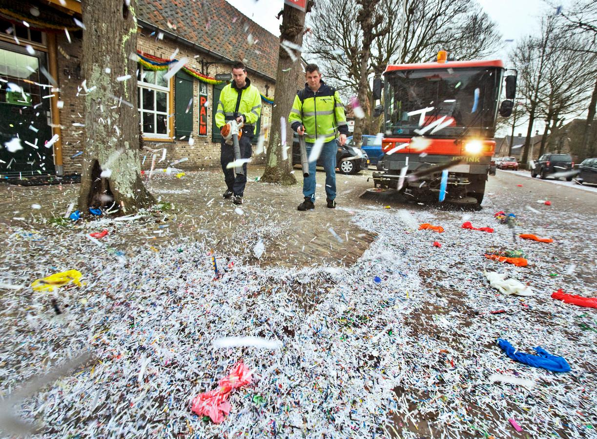Confetti en andere rommel ruimen na de optocht.