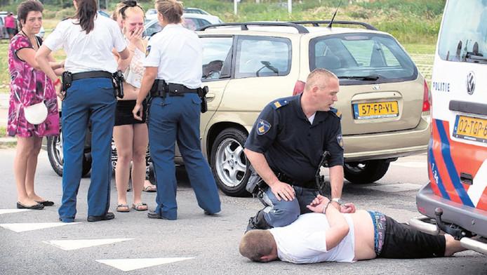 Een agent houdt een man in bedwang, Hij was één van de elf badgasten die gisteravond werden aangehouden.