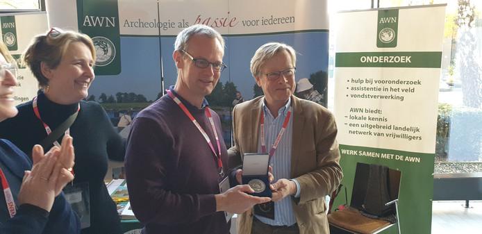 AWN-voorzitter Gajus Scheltema reikt aan de Zutphense stadsarcheoloog Michel Groothedde de legpenning uit.