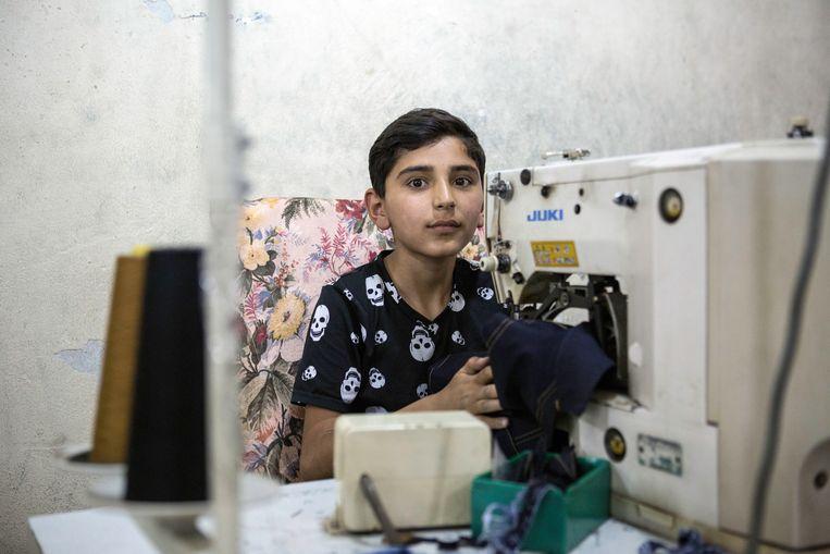 Hamza werkt 10 uur per dag in een naaiatelier in Gaziantep, Turkije om geld te verdienen voor zijn familie. Beeld Hollandse Hoogte