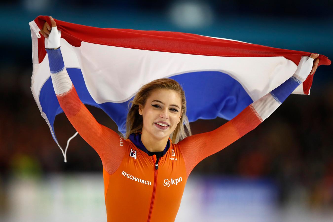 Winnares Jutta Leerdam schaatst met de Nederlandse vlag een ereronde door Thialf.