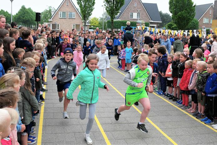 Leerlingen rennen zo hard mogelijk om als eerste over de streep te komen.