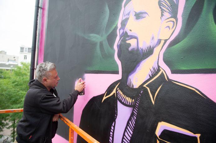 Graffitikunstenaar SMOK werkt aan zijn muurschildering van Matthias Schoenaerts op de Leopoldplaats.