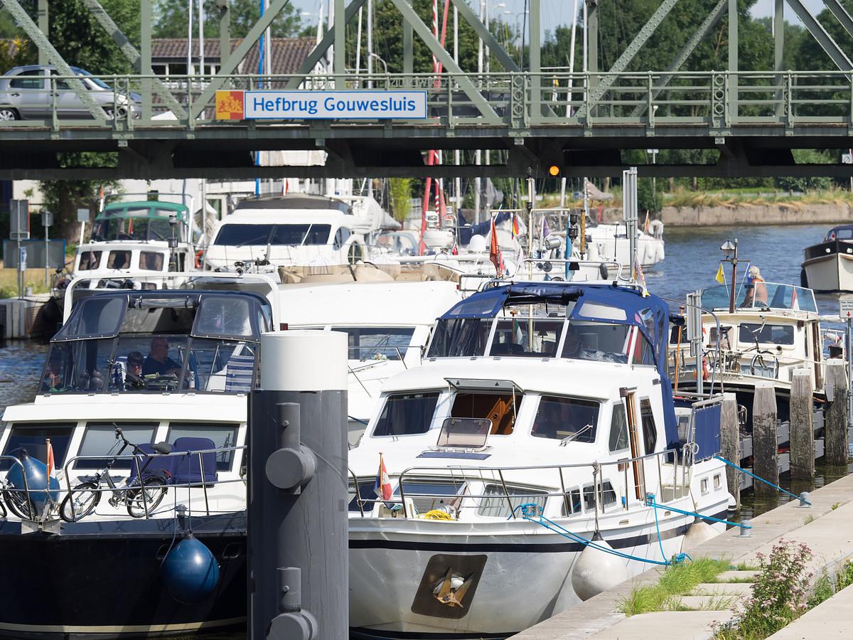 Drukte bij de Alphense hefbrug. Schipper Jan van der V. liet vorig jaar zijn boot onder de geopende brug dobberen, zodat deze niet meer omlaag kon.