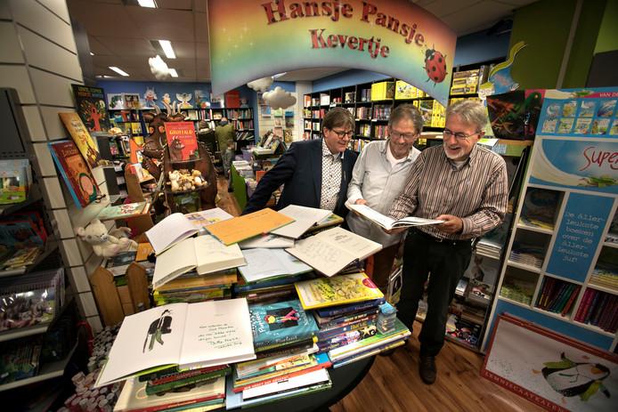 Louis van de Werff, Jacques Vriens en Hans van Gennep met de actie Kinderboeken voor Sint Maarten bij boekhandel de Ganzeveer in Helmond.