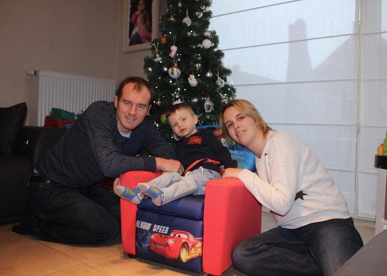 Stijn, Liam en Cindy bij de kerstboom in hun woonkamer: drie stralende gezichten.