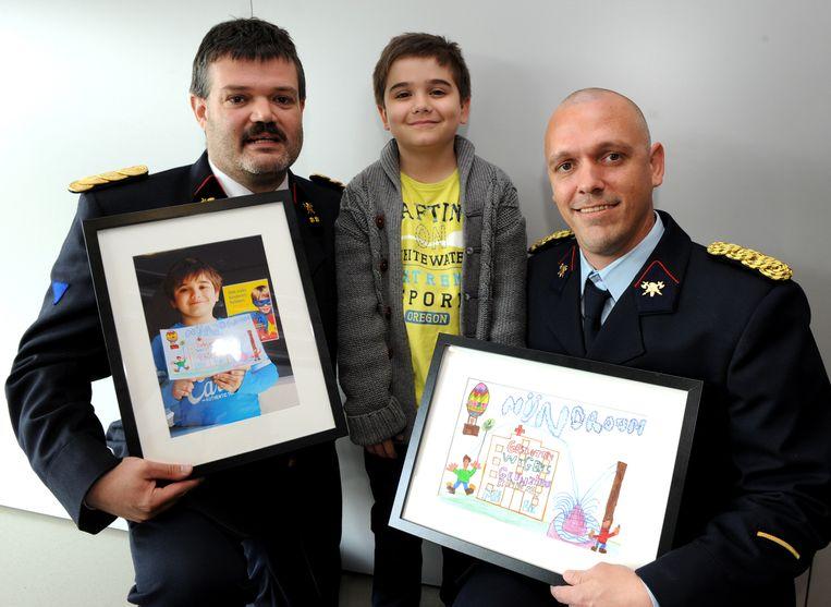 Als dank kregen brandweermannen Bruno Cornelis (links) en Sven De Henau van Luca een fotokader en een ingekaderde tekening.
