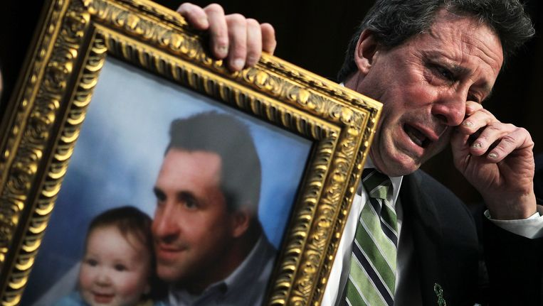 Neil Heslin, vader van het zesjarige slachtoffertje Jesse Lewis, veegt zijn tranen weg terwijl hij een foto omhoogt houdt van zichzelf en zijn zoontje. Heslin werkte mee aan het campagnespotje Beeld Getty Images