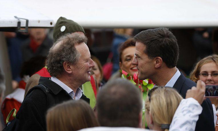 VVD-leider Mark Rutte (rechts) komt GroenLinks-leider Bram van Ojik tegen tijdens het campagne voeren in het centrum van Leeuwarden. Beeld ANP