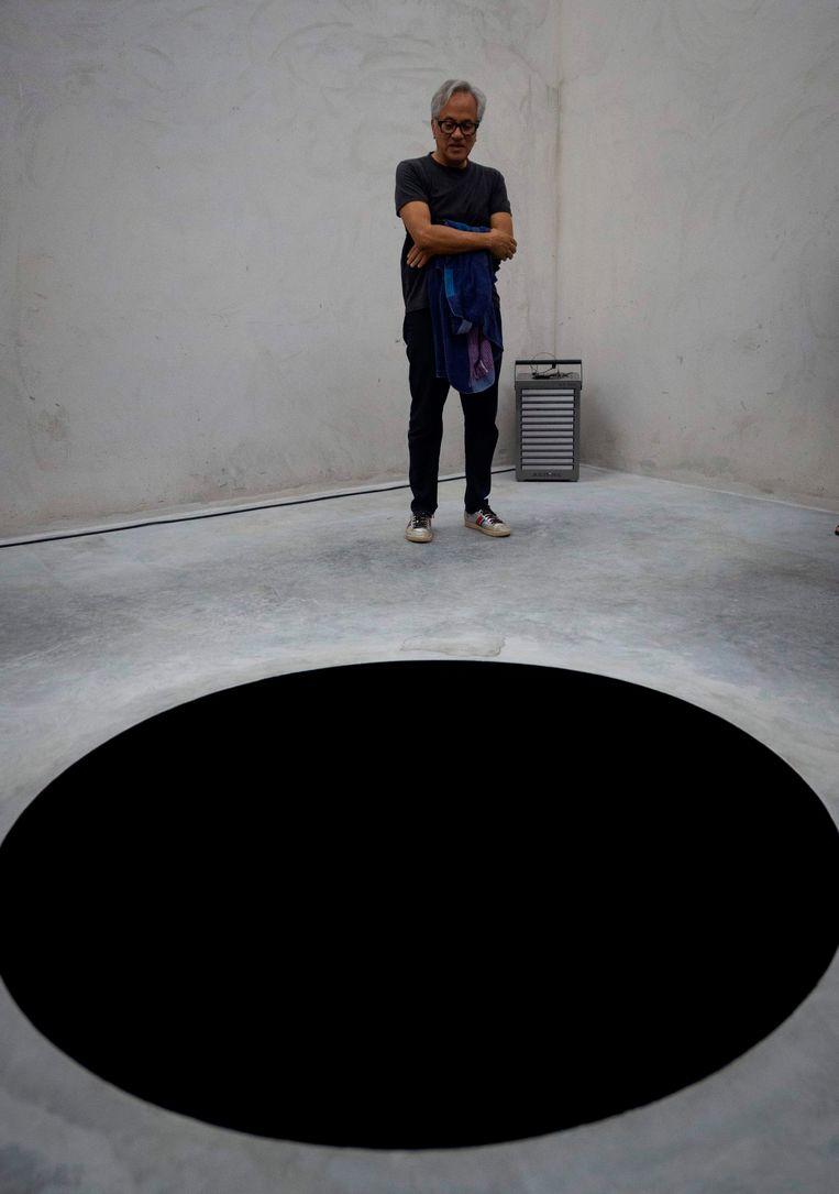 De Britse kunstenaar Anish Kapoor bij zijn werk 'Descent into Limbo'. Beeld AFP