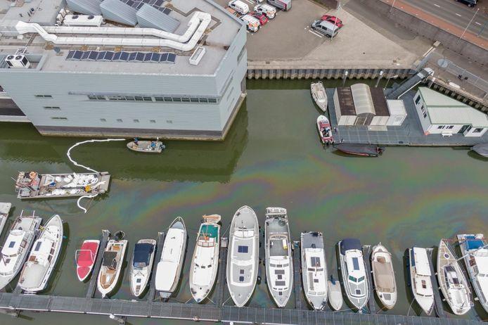 De olie veroorzaakt een gloed over het water van de Alblasserdamse haven