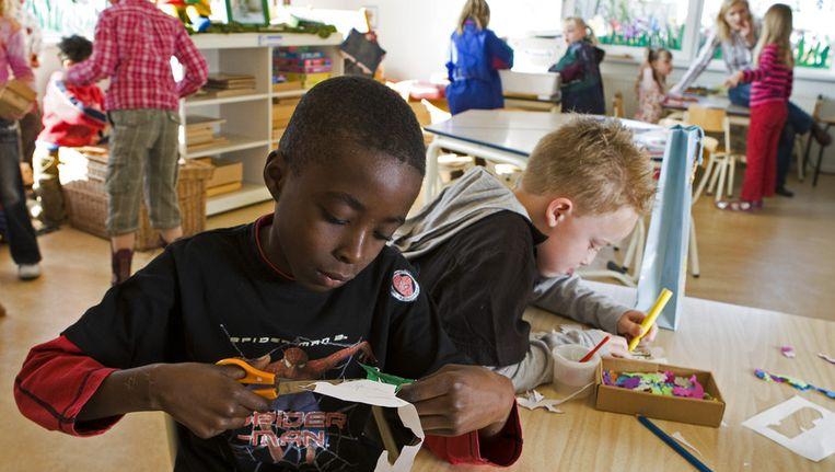 Kinderen op basisschool de Fonkelsteen zijn druk bezig om voor moederdag iets leuks te maken. © ANP Beeld null