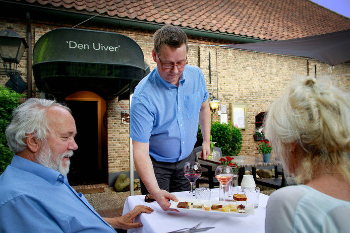 De ervaren bediening serveert een kaasplankje op het terras.
