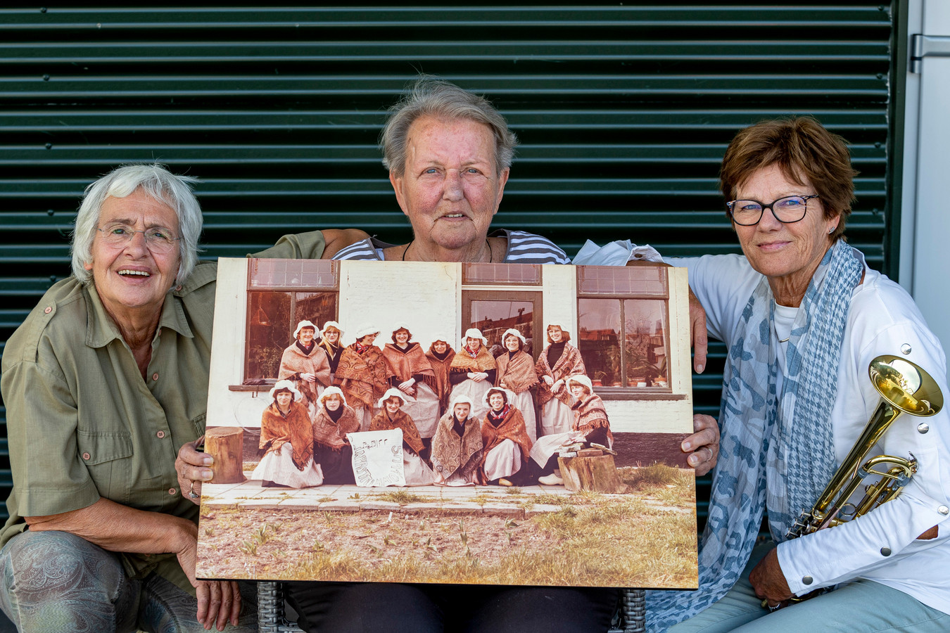 Reünie vrouwelijke dweilband v.l.n.r. : Evelien Jordans, Riet Matthijsen en Helen Bogers met een oude foto van de dweilband destijds. Evelien & Helen waren lid en Riet was in de tijd eigenaar van café de Ster waar de repetities plaats vonden.