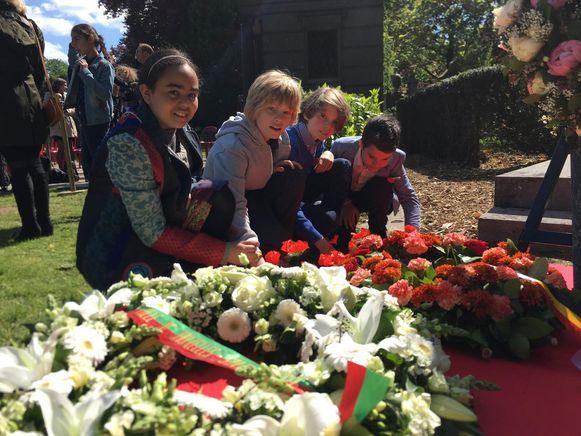 De kinderen van vijf Brusselse scholen leggen bloemen neer aan de graven.