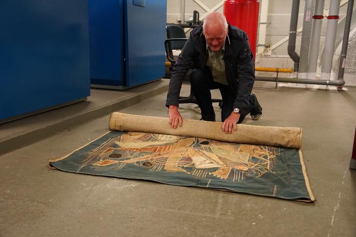 Henk van Gastel, gebouwbeheerder van het Were di, rolt het tapijt van Willi Martinali op.