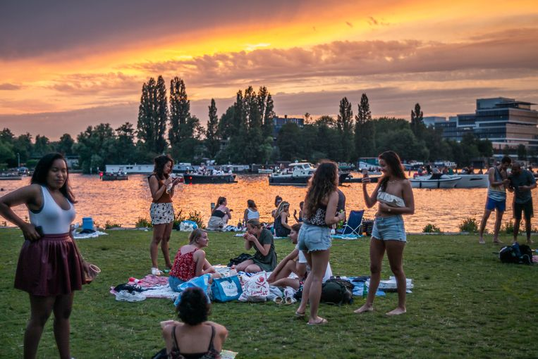 Jongeren vermaken zich bij Park Somerlust op een warme zaterdagavond in Amsterdam. Ondanks het Coronavirus is het vaak (te) druk in de stad. Beeld Joris Van Gennip