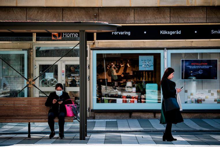 Een vrouw draagt een mondkapje terwijl ze op de bus wacht in Stockholm. Beeld AFP
