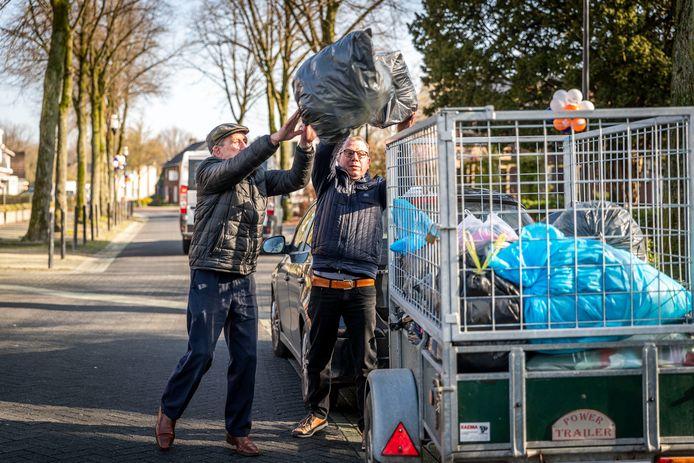 Pa Jan Weijnen (links) en zoon Christiaan in Someren-Eind doen vrijwilligerswerk samen, zoals textiel inzamelen.