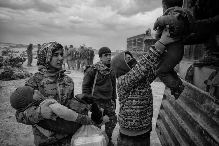 SDF strijders helpen de kinderen die zonder ouders zijn, in een vrachtwagen die hen naar AL Hol Kamp vervoerd.  Beeld Eddy van Wessel