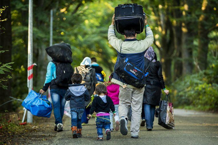 Een kleine groep vluchtelingen verlaat de noodopvang Heumensoord. Beeld anp
