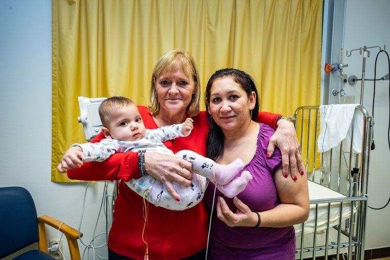 Baby Samia in de armen van onthaalmoeder Martine. Naast haar staat mama Yana.