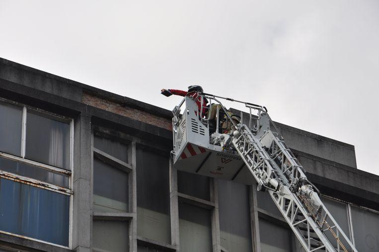 De stadsarchitect (rode trui) schat de schade aan de gevel en het dak in van op de brandweerladder.