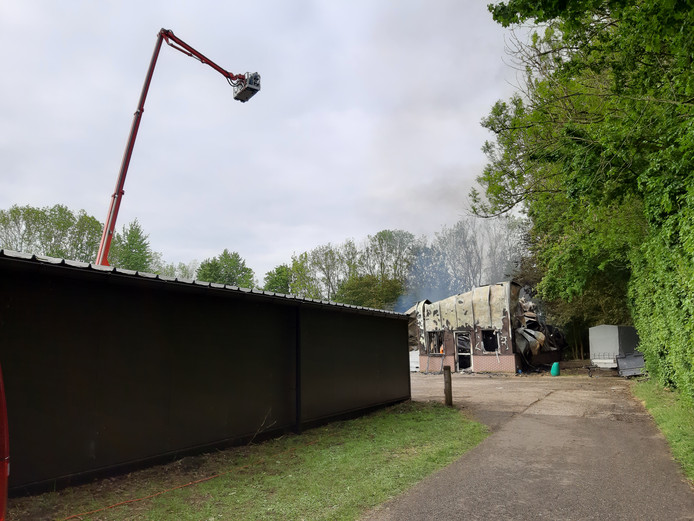 Vanuit de hoogwerker van de brandweer maakt de familie van de eigenaar foto's van de brand.