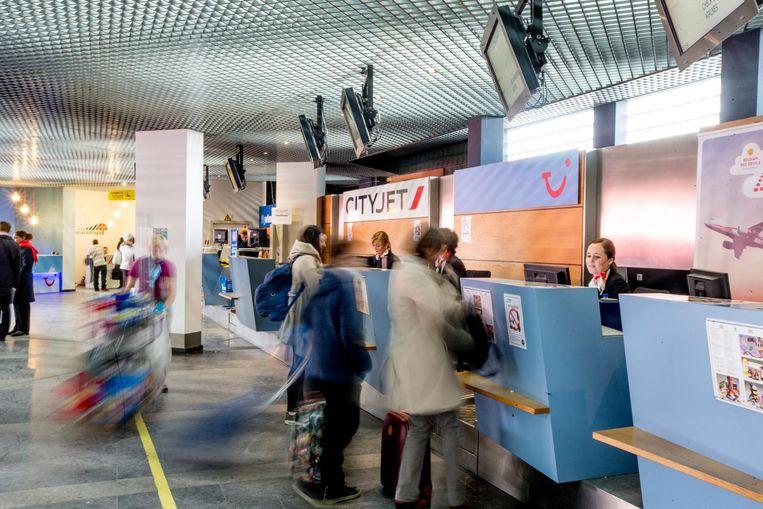 Reizigers en zakenmensen schuiven aan om zich in te checken op Antwerp Airport.