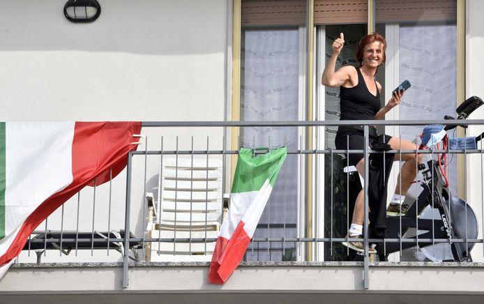 Een vrouw traint op haar hometrainer op het balkon van haar woning in Brignano Gera d'Adda, Noord-Italië.