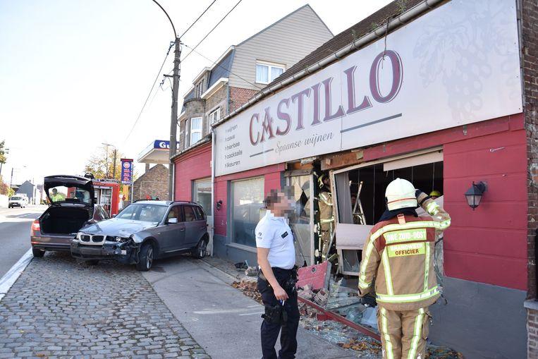 De BMW boorde zich door de geval van de wijnzaak.