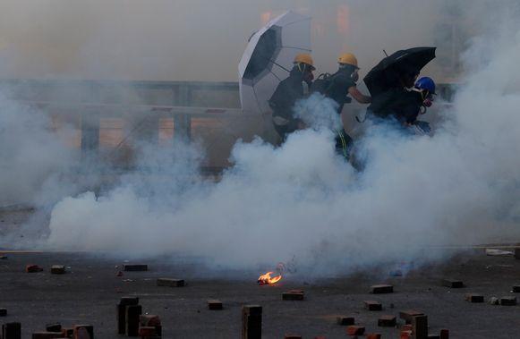 Demonstranten rennen weg van het traangas dat de politie afvuurt aan de universiteitscampus.