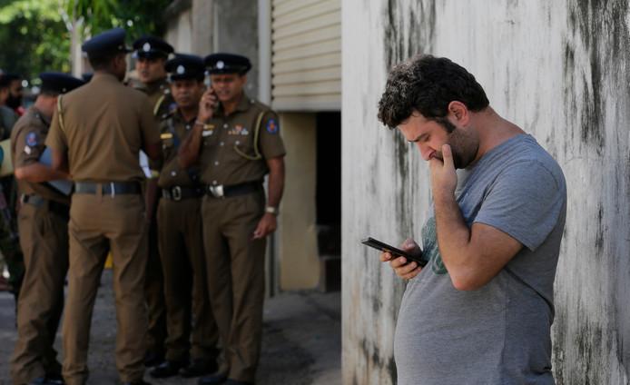 Een toerist in Sri Lanka kijkt, voor het mortuarium van een ziekenhuis, op zijn telefoon.