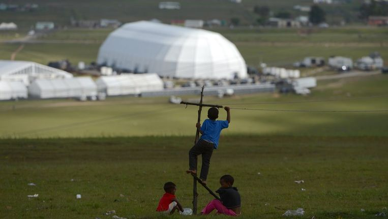 Kinderen spelen voor de tent in Qunu waar de plechtigheid plaatsvindt. Beeld afp