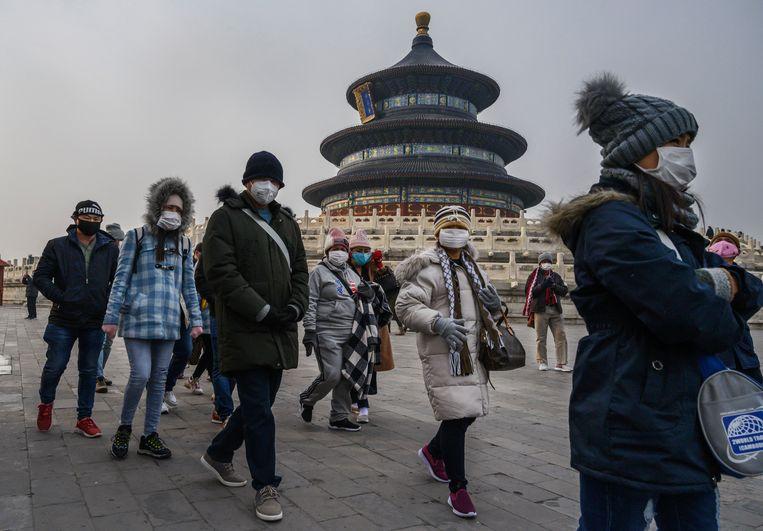 Toeristen dragen mondmaskertjes aan de Tempel van de Hemel in Peking.