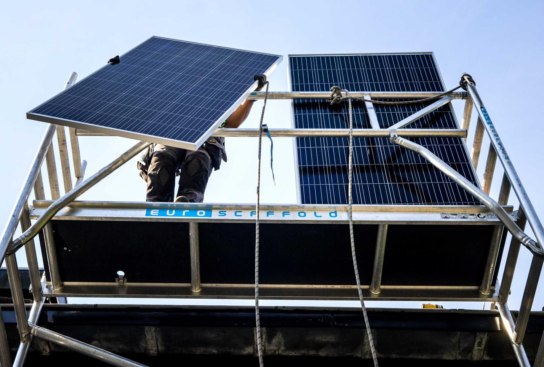 Een installateur plaatst zonnepanelen op het dak van een woonhuis.