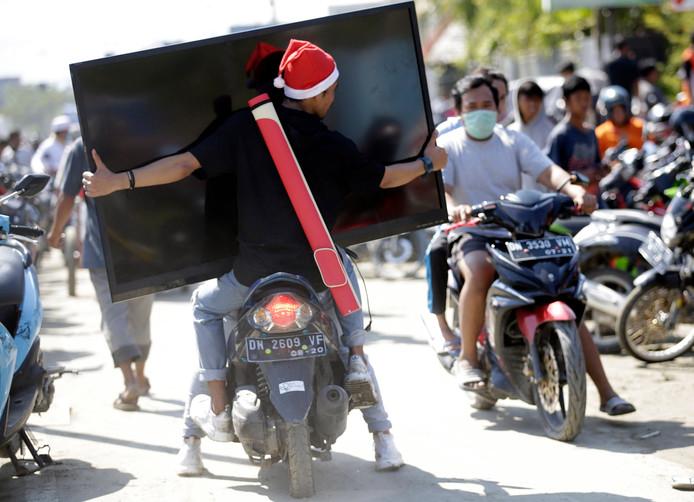 Plunderaars in Palu gaan er vandoor met een breedbeeld televisie.