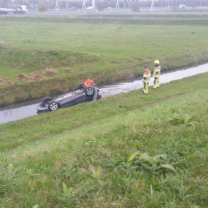De auto op de kop in de sloot langs de A2 bij Geldermalsen.