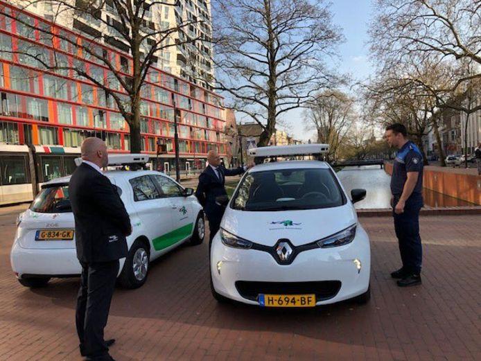 Wethouder Bert Wijbenga (VVD) tussen de camera-auto's. De wagens zijn in opspraak omdat ze op gespannen voet staan met de privacy.