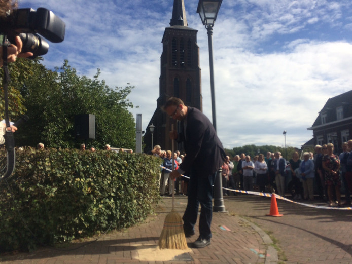 Wethouder Menno Roozendaal veegt de attentietegel - met daarop zand van de 'pastoor zijn berg'- voor de kerk van Eerde schoon.