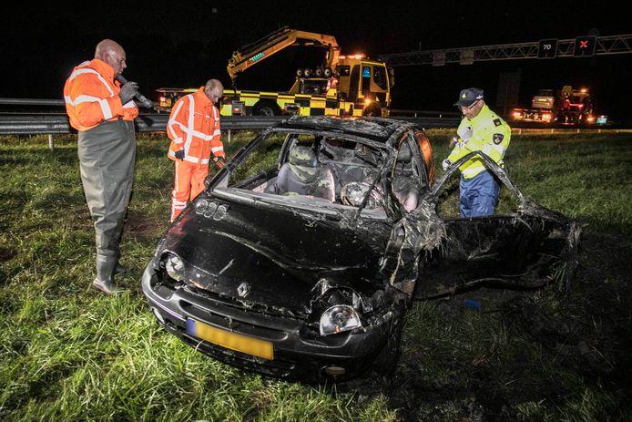 Bergers bij de auto die na het fatale ongeluk op de A325 bij Elst uit de sloot werd gehaald.