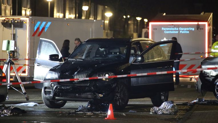 De klemgereden auto van de verdachte wordt in de Knokkestraat, in de Amsterdamse wijk Nieuw-Sloten, onderzocht door forensisch medewerkers van de politie. Beeld anp
