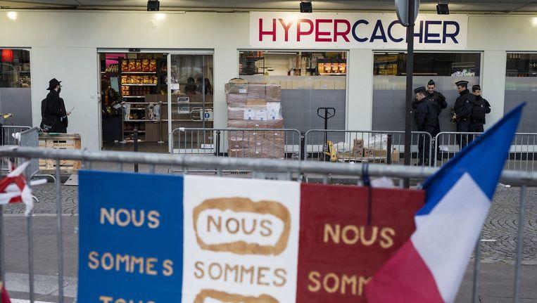 Politieagenten staan op wacht bij de heropening van de joodse supermarkt in Parijs waar in januari een aanslag plaatsvond Beeld epa