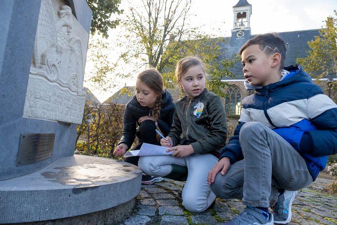 Emily (9) overlegt met Timothy (7) over een opdracht bij het capitulatiemonument in Vrouwenpolder. Links Raisa (8 jaar).